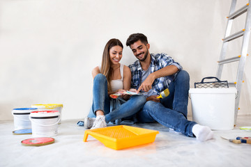 Young happy couple choosing colors for painting their home