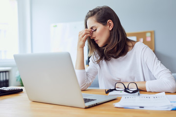 Beautiful stressed young office worker sitting at desk holding head because of pain in office