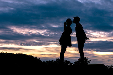 Silhouette couple in love Men ask for married and kissing  on beautiful sunset background , valentine concept