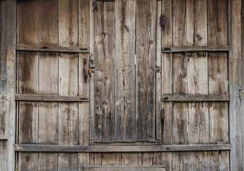 Old brown wooden door embedded in ages wood wall