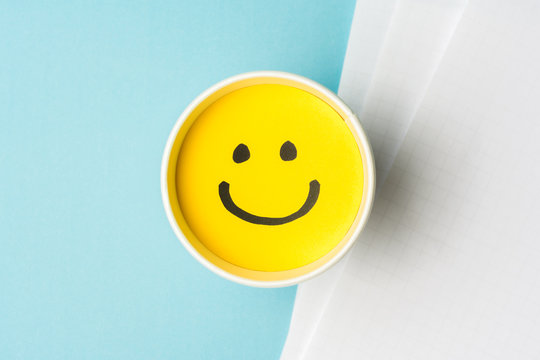 Yellow smiley face or happy emotion, on paper cup and papers over blue background.