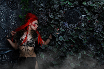 beautiful redhead woman warrior near the dark gothic huge gates