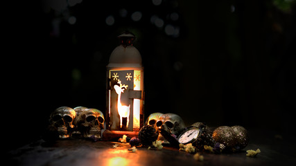 The visual art still life image of human skulls and pile bone with candle Light on old wooden table.