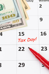 Tax day on calendar with red marker pen, and dollar banknote
