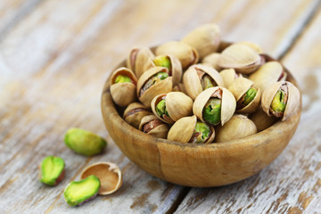 Pistachios with and without shell in bamboo bowl on rustic wooden surface