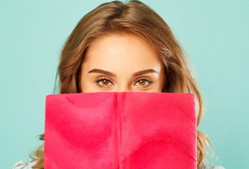 Beautiful young student holding book in front of her face over blue background