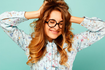 Pretty smiley girl wearing glasses over blue background