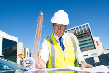 Senior foreman in glasses doing his job at building area on car hood