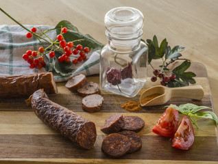 autumn winter still life sausages chili pepper in glass spice jar wooden scoop basil leaves tomatoes and rovan berries on wooden cutting board