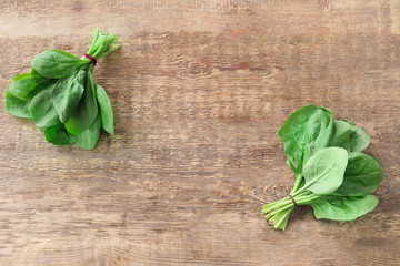Fresh spinach bunches on wooden background