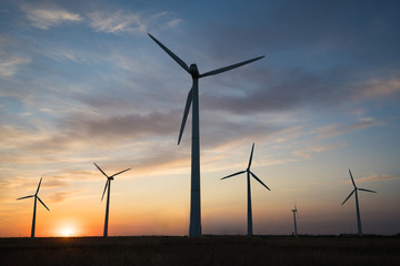 Power generators of windmills at sunset of the day