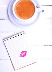 Empty notepad with a lipstick print and a cappuccino