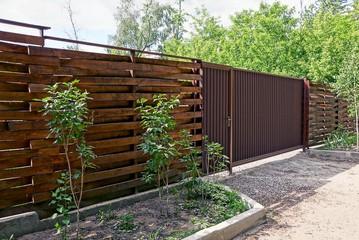 Деревянный коричневый забор и закрытые ворота на улице у дороги
