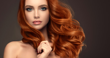 Beautiful model girl with long red curly hair .Red head . Care products ,hair colouring . Wall mural
