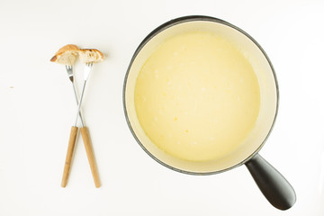 SWISS CHEESE FONDUE WITH BREAD, FORK AND POT ON WHITE BACKGROUND
