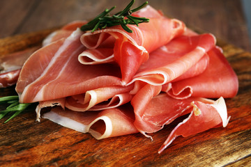 Italian prosciutto crudo or jamon with rosemary. Raw ham.