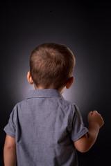 Bimbo ripreso di spalle isolato su sfondo scuro
