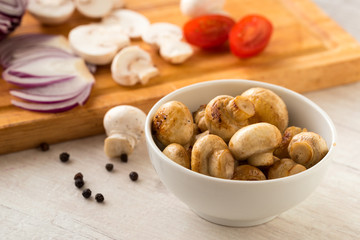 Fried champignon mushrooms in a bowl on the table.