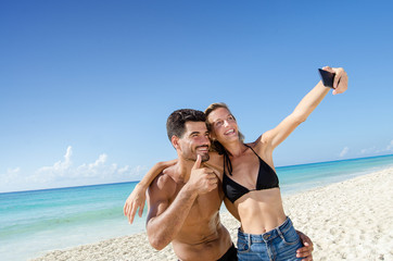 Couple taking selfie photo at the beach