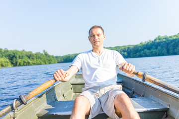 Serious young man rowing boat on lake in Virginia during summer in white shirt