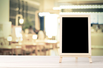 Blank chalkboard standing on wood table over blur cafe with bokeh background, space for text, mock up, food and product display montage