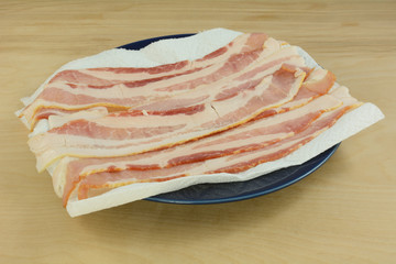 Raw bacon strips on paper towel on blue plate in preparation for microwaving