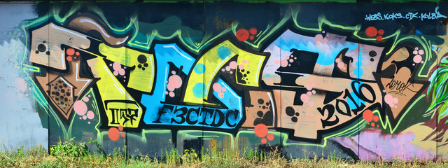 The old wall, painted in color graffiti drawing with aerosol paints. Background image on the theme...