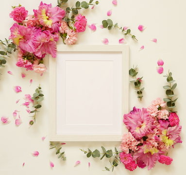 White photo frame and bouquets of pink flowers on a white background. top view. flat lay. copy space