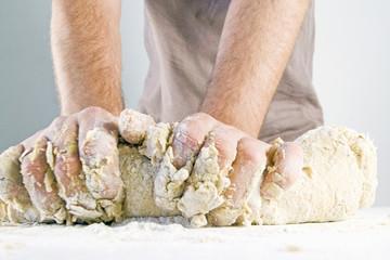 men's hands knead the dough