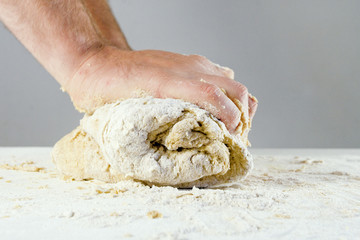 men's hands knead the dough