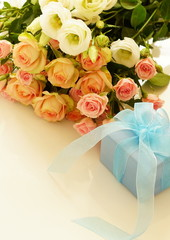 Beautiful bouquet of roses and gift on a white background. top view. Copy space