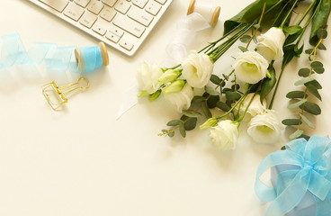 Office table desk with computer, beautiful bouquet white flowers and gift on a white background.women's desk, workspace. top viewCopy space