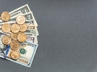 American dollar bills and coins on the gray background.