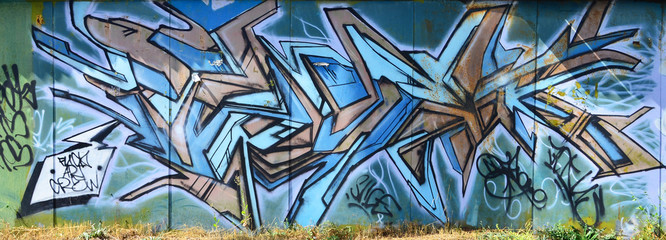 The old wall, painted in color graffiti drawing blue aerosol paints. Background image on the theme...