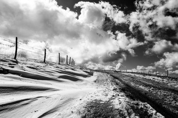 A mountain road with snow at the side, under a deep sky with white clouds