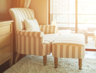 striped armchair with ottoman in living room - sunlight effect