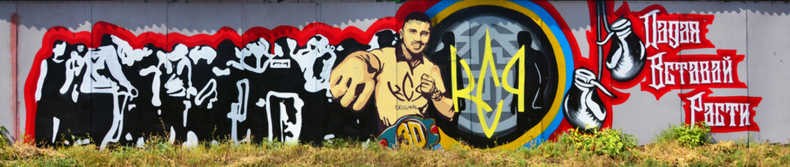 The old wall, painted in color graffiti drawing with aerosol paints. The image of the famous young Ukrainian boxer - Oleksandr Usyk
