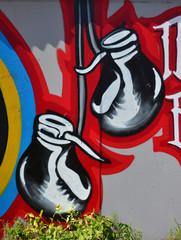 The old wall, painted in color graffiti drawing with aerosol paints. The image of red boxing gloves hanging on the wall