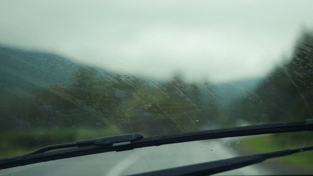 Car wipers removing heavy rain from the windshield during ride in the mountains.