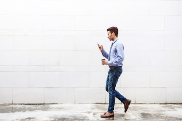Young motivation Businessman using smart phone while walk outdoor building, Lifestyle of modern male, Technology to Communicate in Business concept