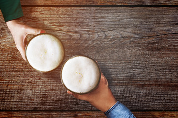 Couple of Man and Woman holding a Glass of Beer to Celebrate in Restaurant or Bar, For Oktoberfest or any Cheerful Event Concept, Top view Over Wooden Table