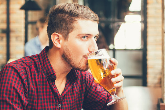 Man Drinking Beer and Using Smartphone in Pub