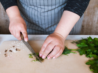 Cook chopping potherbs on wooden cutting board. Cooking process, healthy organic food and decoration, close up picture