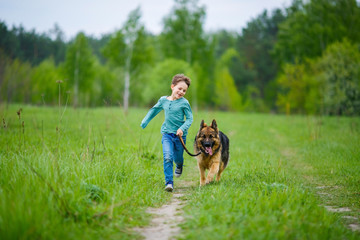 a little boy runs through the green meadow with his big German Shepherd dog. The wind blows his hair