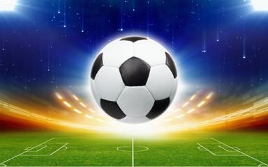 Soccer ball above green football stadium at night