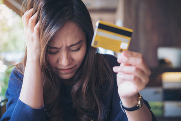 Close up image of an Asian woman close her eyes while holding credit card with feeling stressed and broke