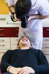 Dentist making photos of female client mouth in hospital.