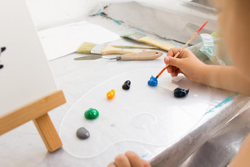 Creative little painter in working process. Artist workplace, early childhood education, interesting hobby for children, craft tools