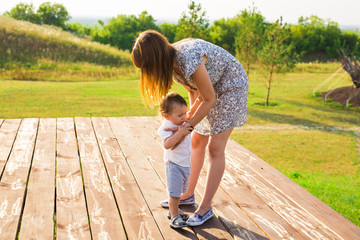 concept of family - mother and child son outdoors in summer