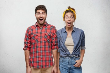 Surprise and astonishment concept. Picture of funny emotional young European couple wearing fashionable clothing expressing shock and full disbelief, amazed with astonishing unexpected news